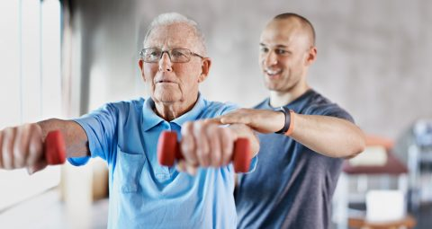 Older adult using light hand weights to improve muscle strength